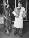 Grocery Store Clerk Carrying Packages For Elegant Woman Reproduction photographique par George Marks