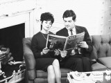 Couple Sitting on Couch, Reading Magazine Photographic Print by George Marks