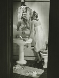 Woman Removing Make Up in Front of Mirror in Bathroom Photographic Print by George Marks