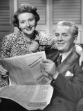 Happy Mature Couple Reading Newspaper Together Photographic Print by George Marks