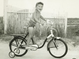 Girl (6-7) Riding Bicycle With Side Wheels Photographic Print by George Marks