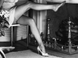 Woman Wearing Stockings Sitting By Fireplace Photographic Print by George Marks