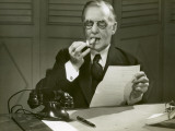 Mature Man Lights Cigar at Desk Photographic Print by George Marks