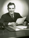 Man Sitting at Desk With Papers Photographic Print by George Marks