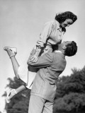 Man Raising Woman in the Air Photographie par George Marks