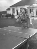 Woman Playing Table Tennis in Garden Photographic Print by George Marks