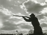 Silhouette of Man Aiming Shotgun Outdoors Photographic Print