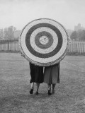 Two Women Holding Up Archery Target in Field Photographie