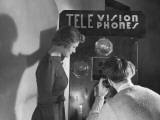 Man and Woman Using Telephone With Video Hookup Photographic Print