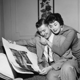 Wife Hugging Husband As He Sits in Armchair, Reading Newspaper Photographic Print