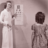 Healthcare Worker Giving Girl (8-10) Eye Examination Photographic Print