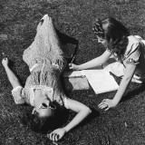 Two Teenage Girls (14-16) on Grass, One Doing Homework Photographic Print