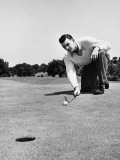 Man Lining Up Golf Shot on Putting Green Photographie