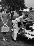 Young Couple Loading Trunk of Car For Picnic Photographic Print