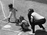 Two Boys Playing Baseball; Adult Umpire Standing Behind Home Plate Photographic Print