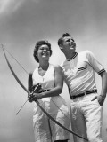 Man Standing Beside Woman Who is Holding Bow and Arrow Photographic Print