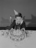 Boy Sitting at Table With Birthday Cake, Portrait Photographic Print by George Marks