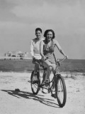 Teenage Boy and Girl Riding Bike Along Beach Photographic Print