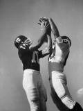 Two Football Players Jumping For Ball at Same Time Photographic Print