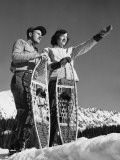 Couple Holding Snowshoes, Woman Pointing Papier Photo