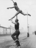 Male Acrobat on Unicycle Supporting Woman in Air Photographic Print