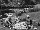 Family Having Picnic By Pond Photographic Print