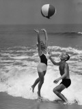 Young Couple Playing With Beach Ball at Water's Edge Photographic Print