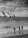 Tres niños corriendo en la playa, siguiendo a cuatro veleros en el océano Lámina fotográfica