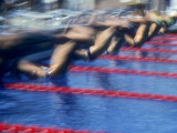 Blurred Action of Male Swimmers at the Start of a Race Photographic Print