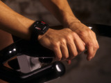 Detail of Hands on Stationary Bike with Heart Rate Monitor Watch Photographic Print