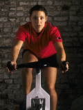 Young Woman Exercising on a Stationary Bike Photographic Print