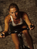 Young Woman Exercising on a Stationary Bike Reproduction photographique