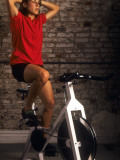 Young Woman Exercising on a Stationary Bike Fotoprint