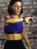 Young Woman Exercising on a Stationary Bike Checking her Heart Rate Photographie