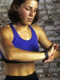 Young Woman Exercising on a Stationary Bike Checking her Heart Rate Photographic Print