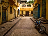 Back Street of Luxor Town, Egypt with Motorbike Photographie par Clive Nolan
