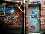 Derelict Door with Graffiti 2 Photographic Print by Clive Nolan