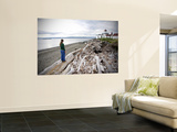 Woman Standing on Driftwood and Looking Towards Discovery Park Lighthouse Wall Mural by Micah Wright