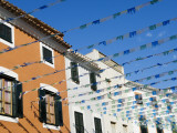 Spain, Menorca; Bunting over a Street in Es Mercadal Photographic Print by John Warburton-lee
