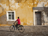 Mozambique, Ihla De Moçambique, Stone Town; a Boy Cycles Through the Cobbled Streets of Stone Town Fotografie-Druck von Niels Van Gijn