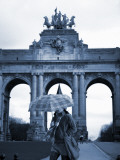 Belgium, Brussels; a Girl Walking with an Umbrella in Front of the Arc Du Triomphe Photographic Print by Ken Sciclina