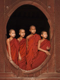 Myanmar, Burma, Nyaungshwe; Young Novice Monks Standing at a Wooden Oval Window Photographic Print by Katie Garrod