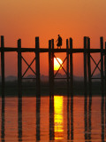 Myanmar (Burma), Amarapura, Taungthaman Lake, U Bein's Bridge, a Monk Walking Home at Sunset Photographic Print by Katie Garrod