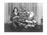 Woman at Christmas Tree with Cut-Out Santa Prints