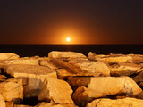 The Moon Rising Behind Rocks Lit by a Nearby Fire in Miramar, Argentina Photographic Print by  Stocktrek Images