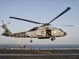 A US Navy SH-60F Seahawk Hovers Above the Flight Deck of USS Eisenhower Photographic Print by  Stocktrek Images