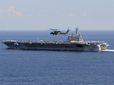 An MH-60S Seahawk Helicopter Flies over USS George H.W. Bush Photographic Print by  Stocktrek Images