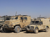 A British Armed Forces Snatch Land Rover Parked Next to Other Military Vehicles Photographic Print by  Stocktrek Images