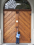 Young Boy Reaches for Door Handle at St. Peter's Church Photographic Print by  Greg