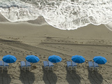 Umbrellas on a Beach with Approaching Surf at Sunrise Photographic Print by Paul Sutherland